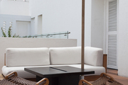 A whitewashed seating area with teak chairs and an umbrella.