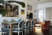 Large scale art hanging in a dining area with victorian chairs and rustic table.