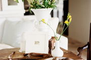 A rustic tabletop decorated with art, flowers, and decorative objects