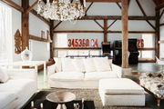 White couches and a crystal chandelier in a barn