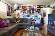 A living room with a gray sectional couch and a colorful gallery wall.