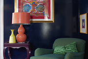 A navy blue lacquered family room featuring a green upholstered arm chair and colorful art and accessories.