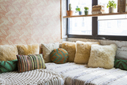 Shaggy throw pillows in cozy couch nook.