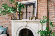 A marble fireplace against a brick wall.