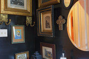 Black lacquered walls and framed artwork  in a guest bathroom