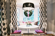 A mix of patterns in a breakfast nook with a white tulip-style table and a window seat