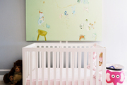 A painting hung above a white crib in a nursery