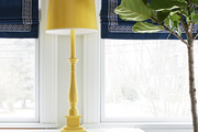 An oversize table lamp spray-painted bright yellow accents a traditional sunroom with a fiddle leaf fig.