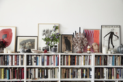 A white bookshelf with decor and art.