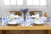 A wooden dining table set with hurricane vases, dried lavender, and a blue-and-white runner
