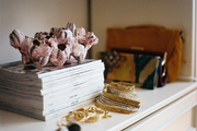 A white shelf decorated with clutches, jewelry, and a stack of magazines