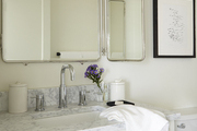 Silver bathroom mirror above marble sink.