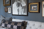 An eclectic gallery wall against dark paint over a tufted sofa