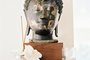 A Buddha-head statue on a wooden side table