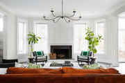 Large window-lit living room with tall potted plants and bright patterned furniture.