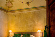 A bedroom in Italy with frescoed ceilings and terrazzo floors