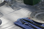 Embroidered table cloth atop outside dining table.