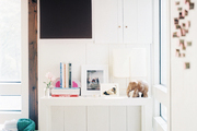 A corner vignette formed with a Parsons table and styled with framed photos and books