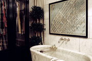 Basket-weave tile paired with an oval tub and a framed map