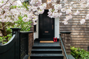 A blossom-lined walkway to a black front door