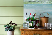The painting on a burled-wood cabinet and bar in the den conceals the television.