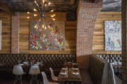 A brick archway over tufted leather banquettes, dining tables, and artwork at the District Miami
