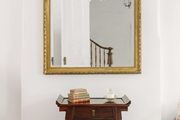 An antique wooden side table in front of a gilded mirror.