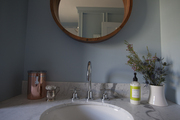 Round mirror above silver sink faucet and marble countertop.