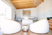 White accent chairs in a minimalist room with wood beamed ceilings.