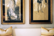 Framed artwork above a bench with striped pillows