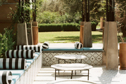 A poolside outdoor lounge area with striped pillows