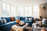 A blue sectional couch, striped armchairs, and a tufted ottoman in a family space
