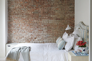 Exposed Brick and rafters in window lit bedroom.