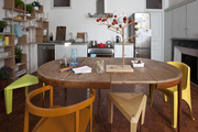 Rustic kitchen dining table with modern chairs.