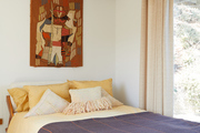 A colorful bed with frilled throw pillows and a bedroom hanging art piece.