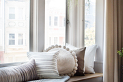 A window bench with neutral pillows.