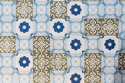 A detail of blue and white tiles on a wall outside.
