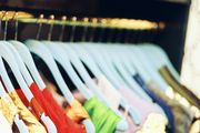 Clothing organized on blue hangers in a walk-in closet
