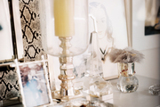 A hurricane lamp and a collection of glass, crystal, and Lucite on a white chest of drawers