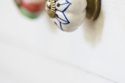 Hand-painted knobs on white drawers in a kitchen