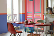 Colorful doors and a red-topped table, as well as a fireplace topped by a gold mirror, in a Paris dining room