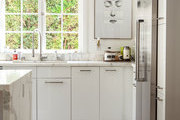 A pared-down white kitchen with marble accents