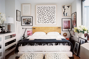 A wall of framed art hung above a burlwood headboard