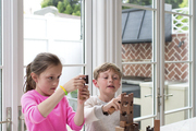 Eight-year-old twins at play in a kitchen with French doors