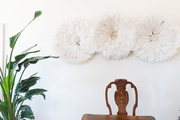A detail of three white African juju hats above a dining table.