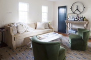 Blue pops of color on a living room's door and rug brighten otherwise subdued decor