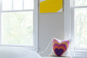 Accenting art hanging above a clear-backed seat with a colorful pillow.