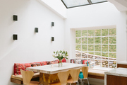 A modern bright dining space with wooden dining chairs.