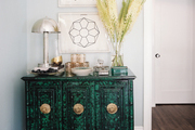 Framed art hung above a malachite console