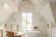 A Sputnik chandelier hanging from an a-frame ceiling with a freestanding tub below